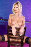 Brooke Banner glorious naked boobs hang over the back of the chair she straddles!