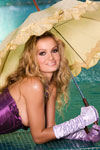 Prinzzess braves a rare California sun shower in her gartered and corseted buff underneath a dainty parasol.
